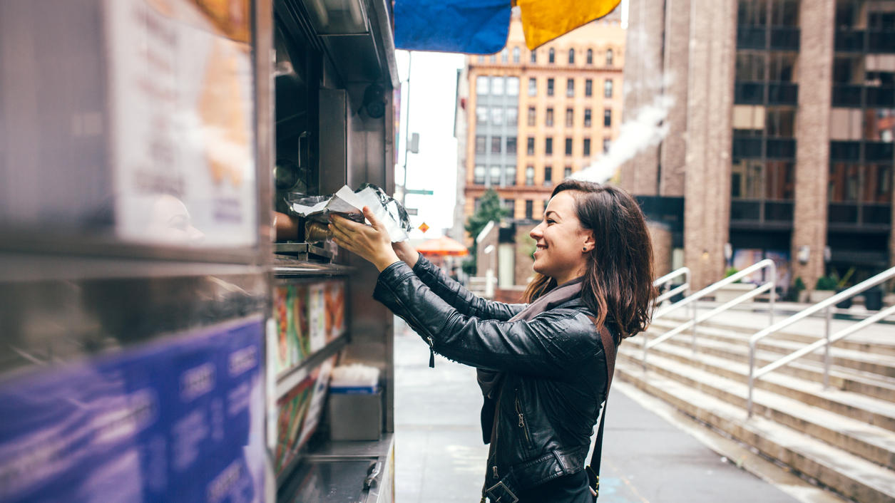 A beautiful Caucasian adult woman buys some lunch from a New York city food cart, a smile on her face.  She wears modern stylish clothing with darker and black colors.  Horizontal image with copy  space.