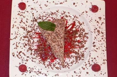 Eistorte auf Himbeerspiegel mit Schokoraspeln und Minzblatt - Rezept