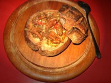 Wildgulaschsuppe im Brot serviert - Rezept