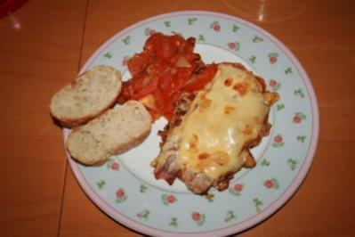 Schnitzel mit Parmaschinken und zerlaufenem Käse an Tomaten - Rezept