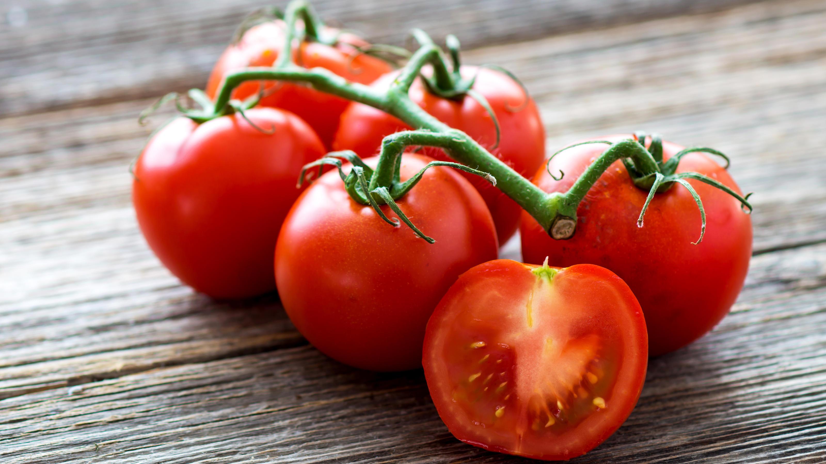 Sechs rote Tomaten liegen auf einem dunkelbraunen Holztisch