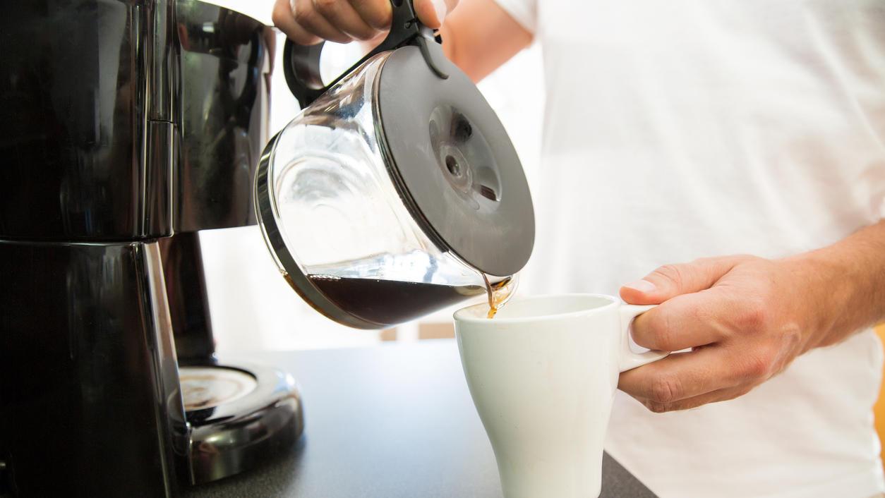Ein Mann gießt sich am Morgen eine Tasse Kaffee aus einer Filtermaschine ein.