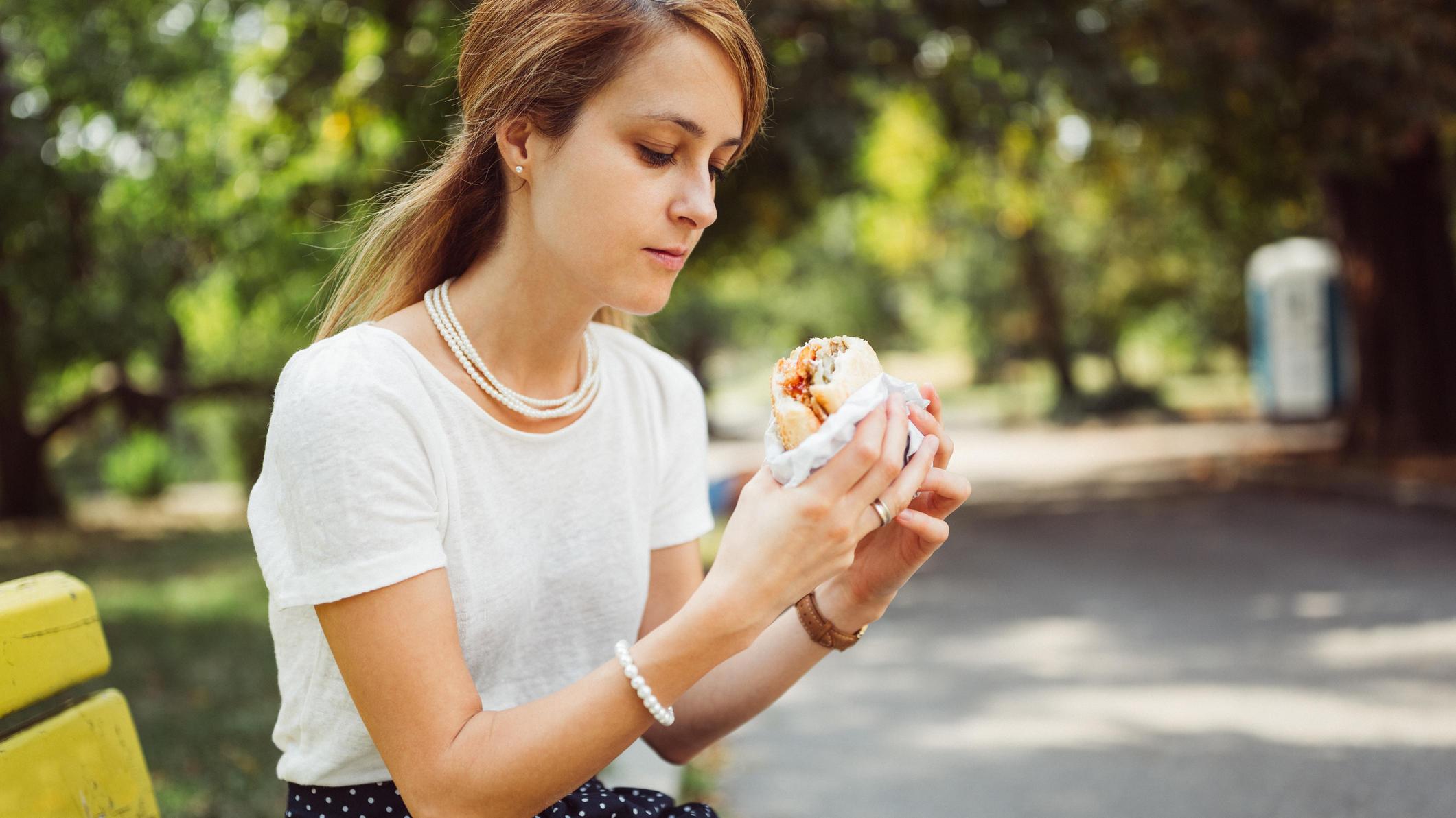 Frau ist Burger alleine im Park.