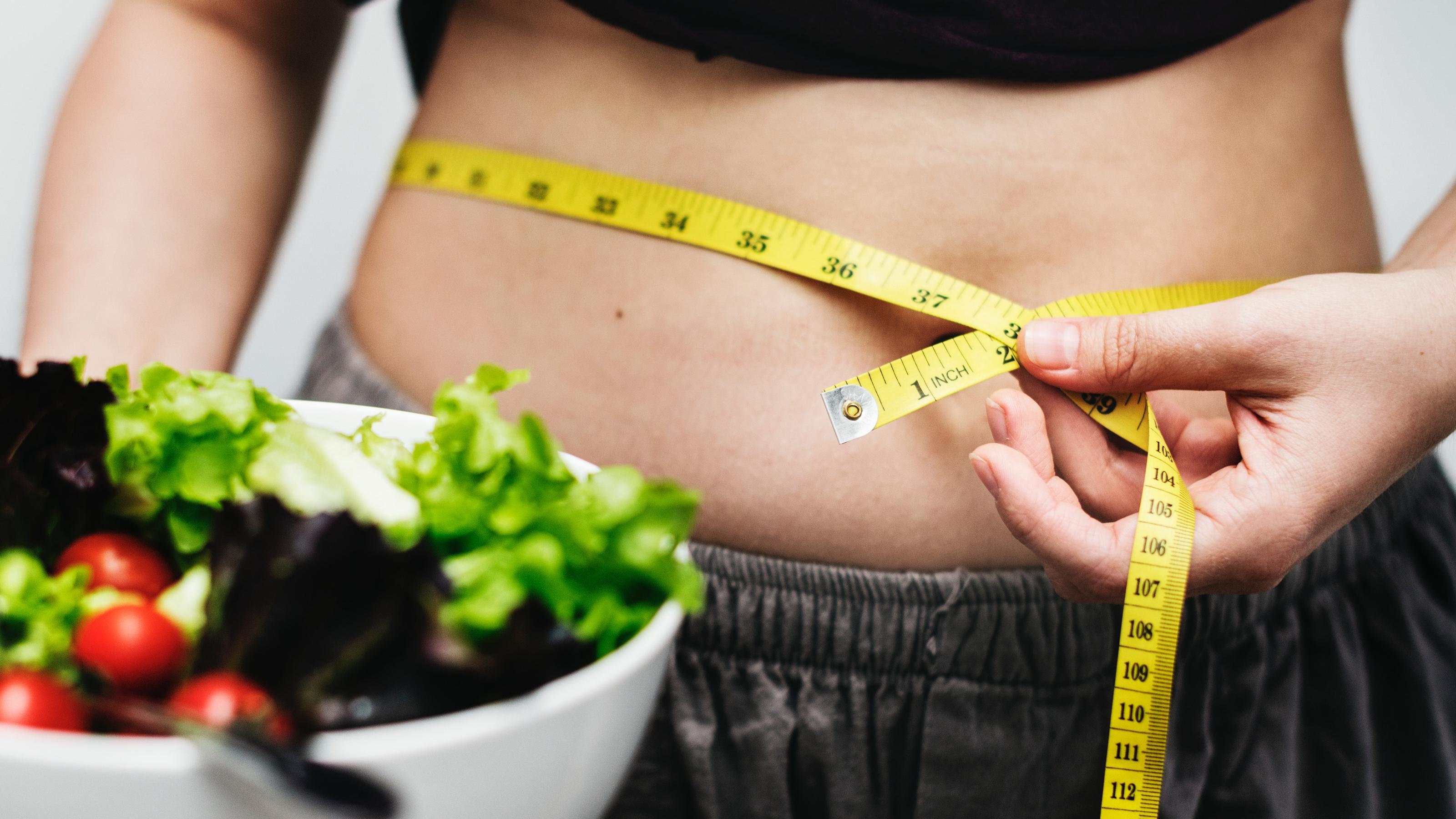 Frau mit Salat und Maßband um den Bauch