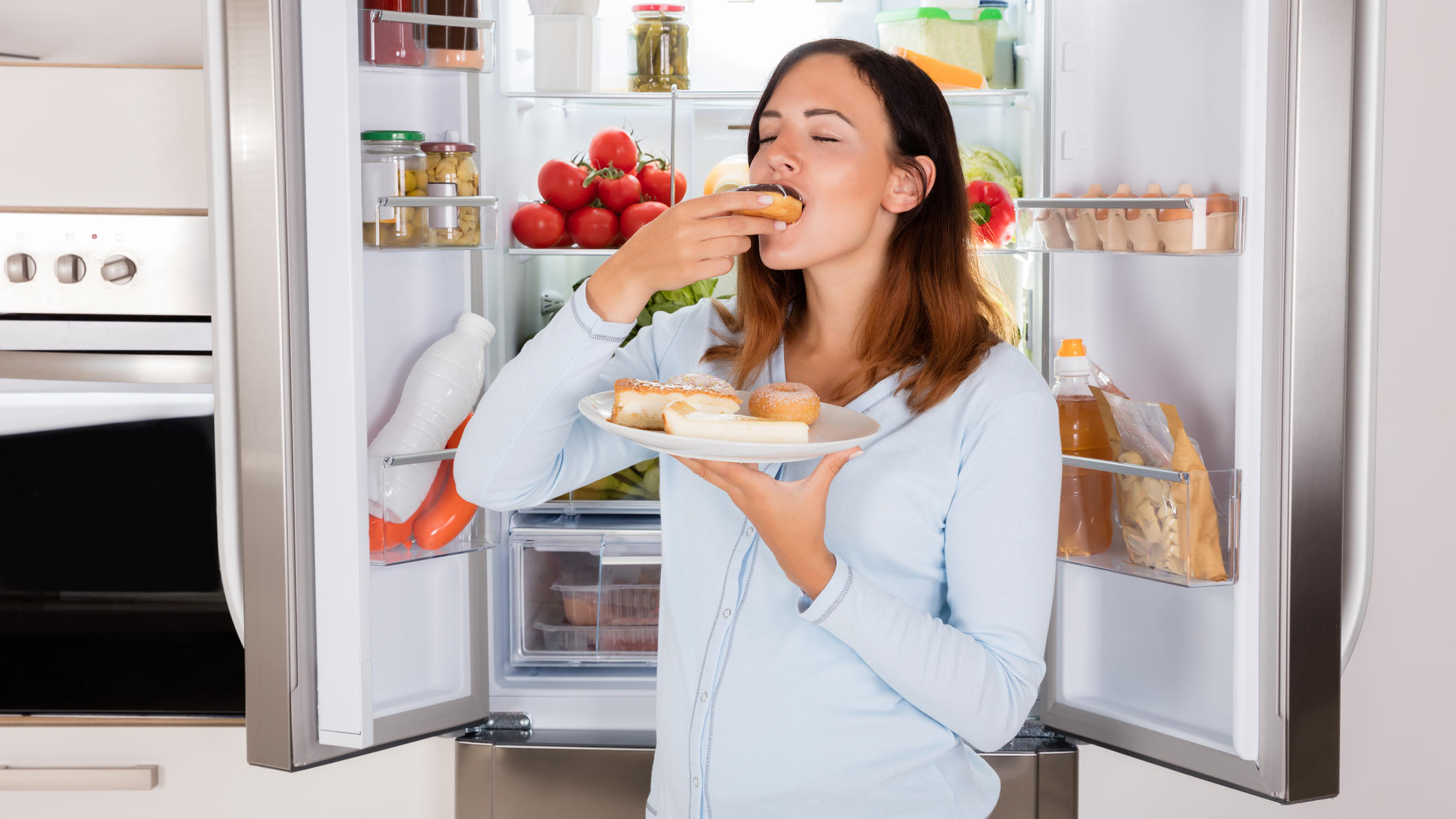 Frau isst vorm geöffneten Kühlschrank