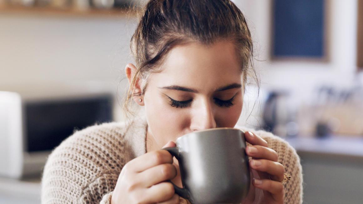Frau trinkt Kaffee aus Kapselmaschine