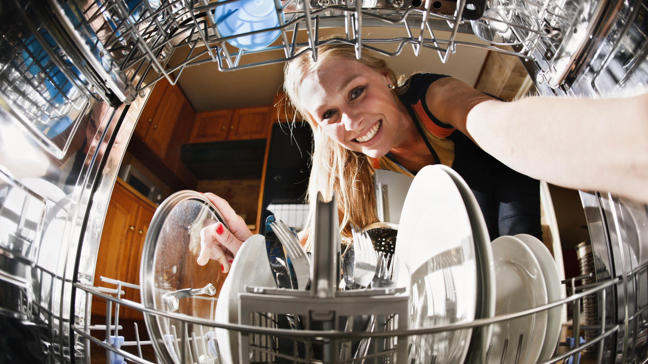 Junge Frau räumt die Spülmaschine ein