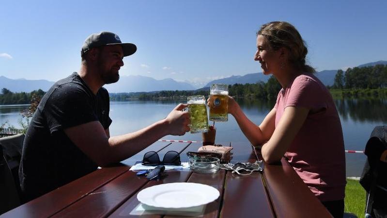 Ein Paar genießt ein gemeinsames Bier in der Sonne in einem Biergarten