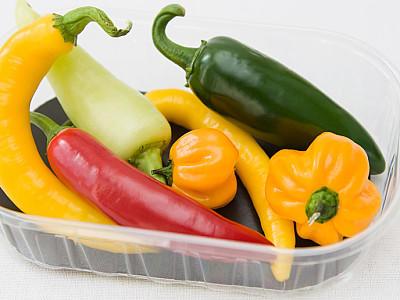 Plastikschachtel mit verschiedenen Sorten von Chilischoten und Peperoni vor weißem Hintergrund.Plasticbox with different kind of chillies and peppers and white background.