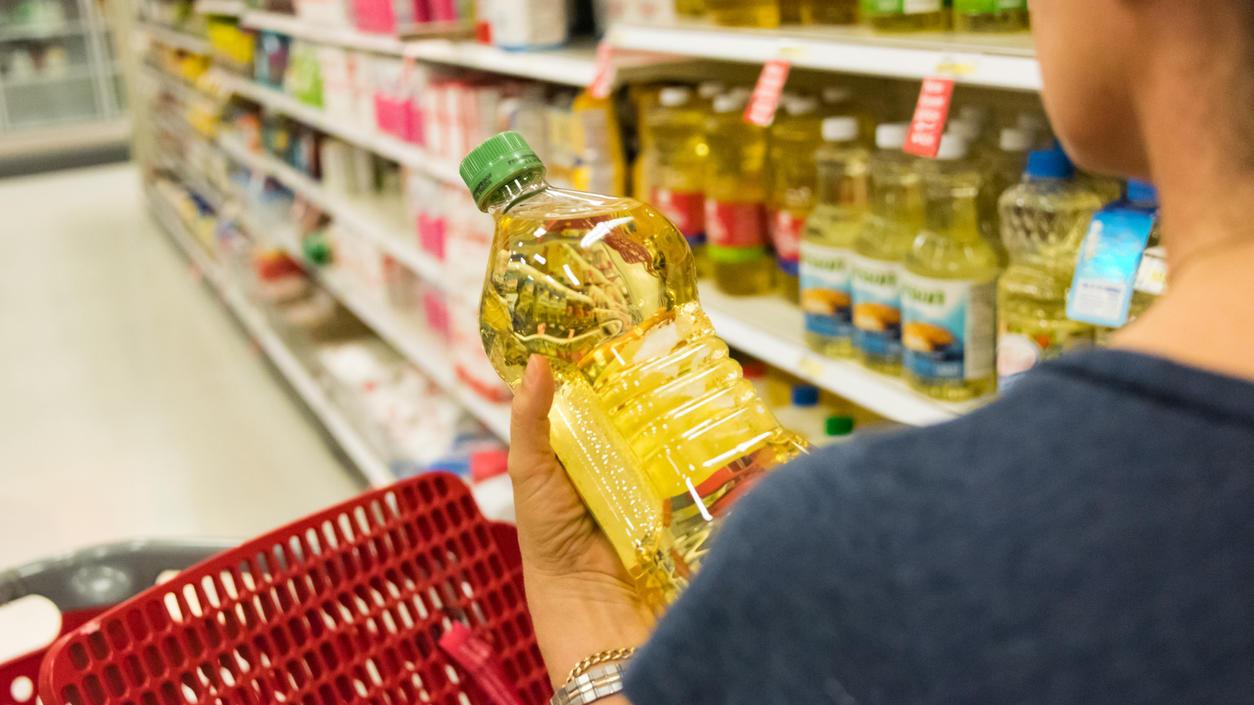 Frau kauft Pflanzenöl im Supermarkt ein