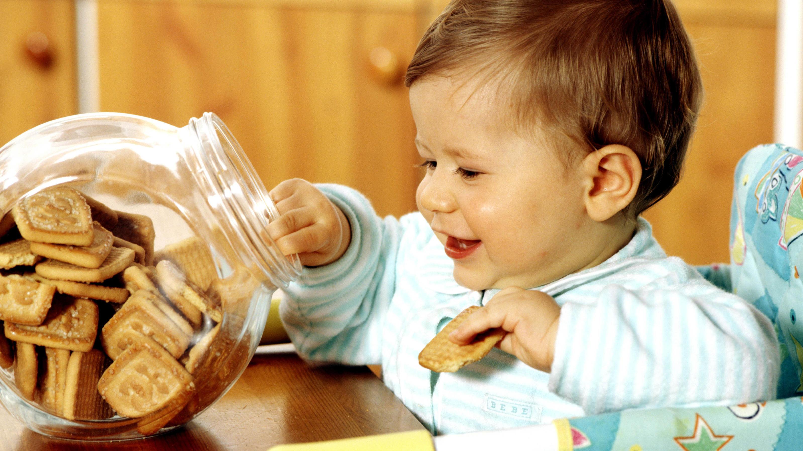 Baby greift nach Keksdose