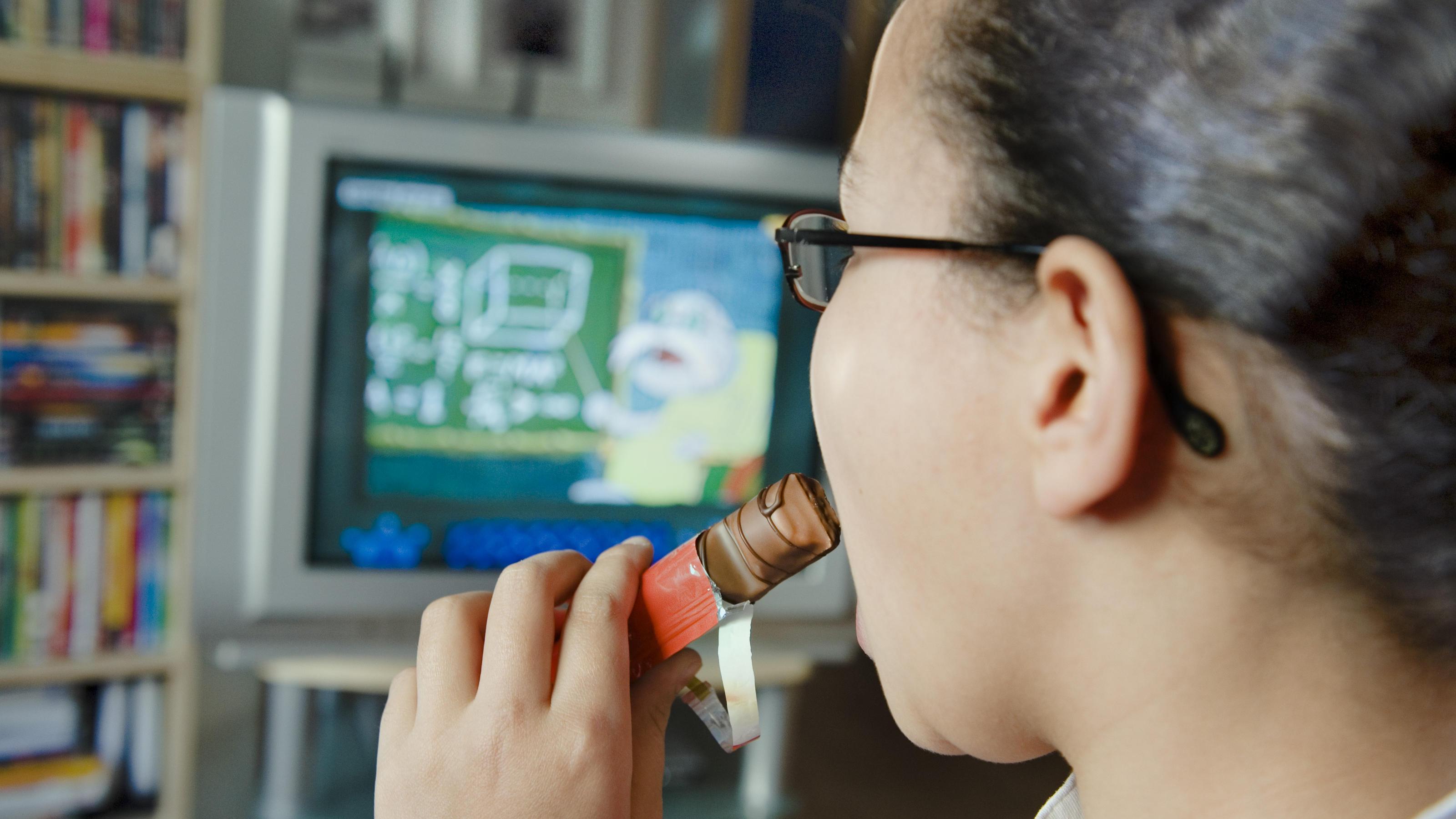Ein zehn Jahre altes Mädchen aus Hamburg isst vor dem Fernseher Süssigkeiten (Foto vom 14.04.2008). 15 Prozent der Kinder und Jugendlichen in Deutschland sind übergewichtig. Die Bundesregierung will den überflüssigen Pfunden von Jugendlichen zu Leibe