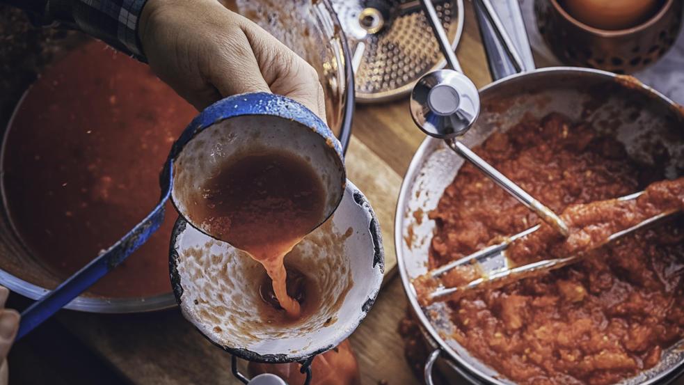 Tomaten mit der Hand zu passieren macht Arbeit und Schmutz