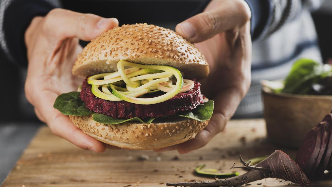 Ein junger Mann hält einen appetitlichen Veggie-Burger in der Hand