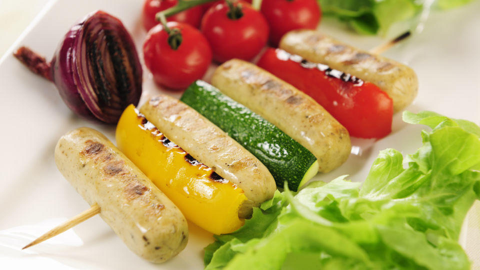 Grilled vegetables and sausage on a stick with side garnish; selective focus