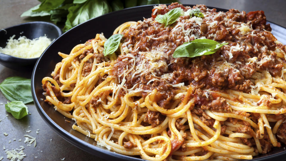 Spaghetti bolognese in black serving platter, with fresh basil and parmesan.