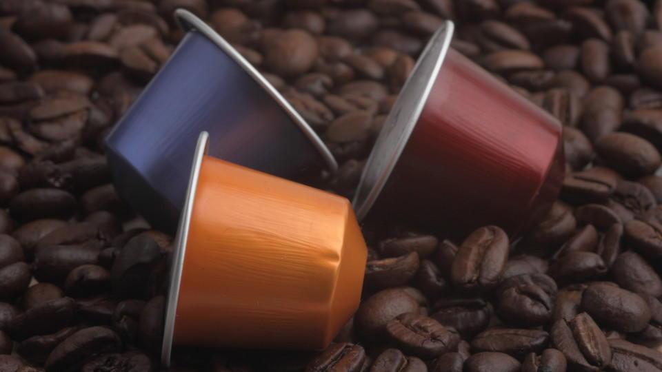 Drei Kaffeekapseln auf einem Haufen Kaffeebohnen