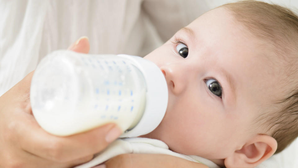A detail shot of cute baby drinking milk from bootle