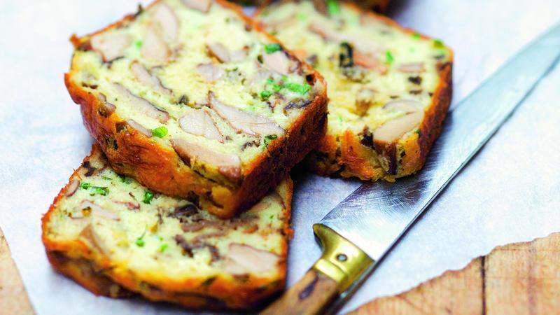 Aufgeschnittenes Brot liegt auf einem Holzbrett mit einem Messer daneben.