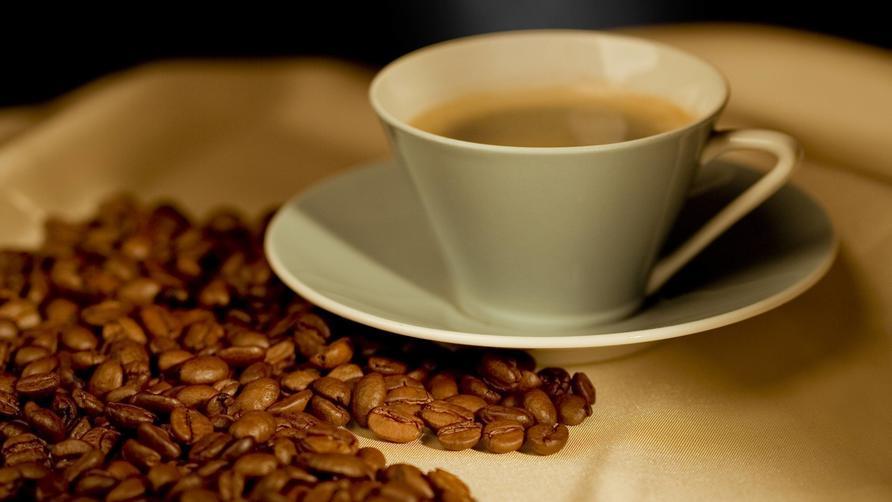 Eine Tasse Kaffee neben Kaffeebohnen.