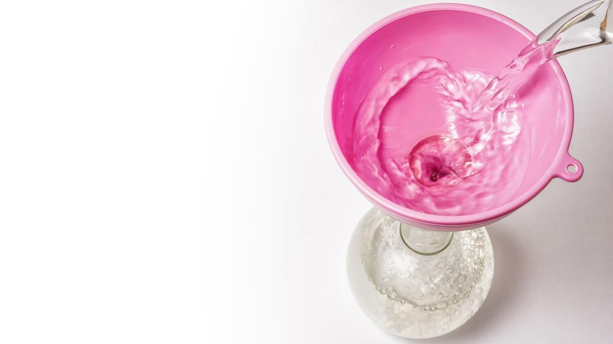 Wasser wird durch einen Trichter in ein Gefäß gefüllt.