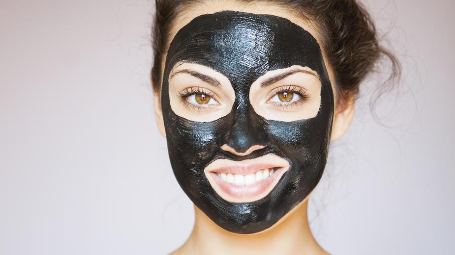 Eine junge Frau hat eine Gesichtsmaske mit Aktivkohle aufgetragen.
