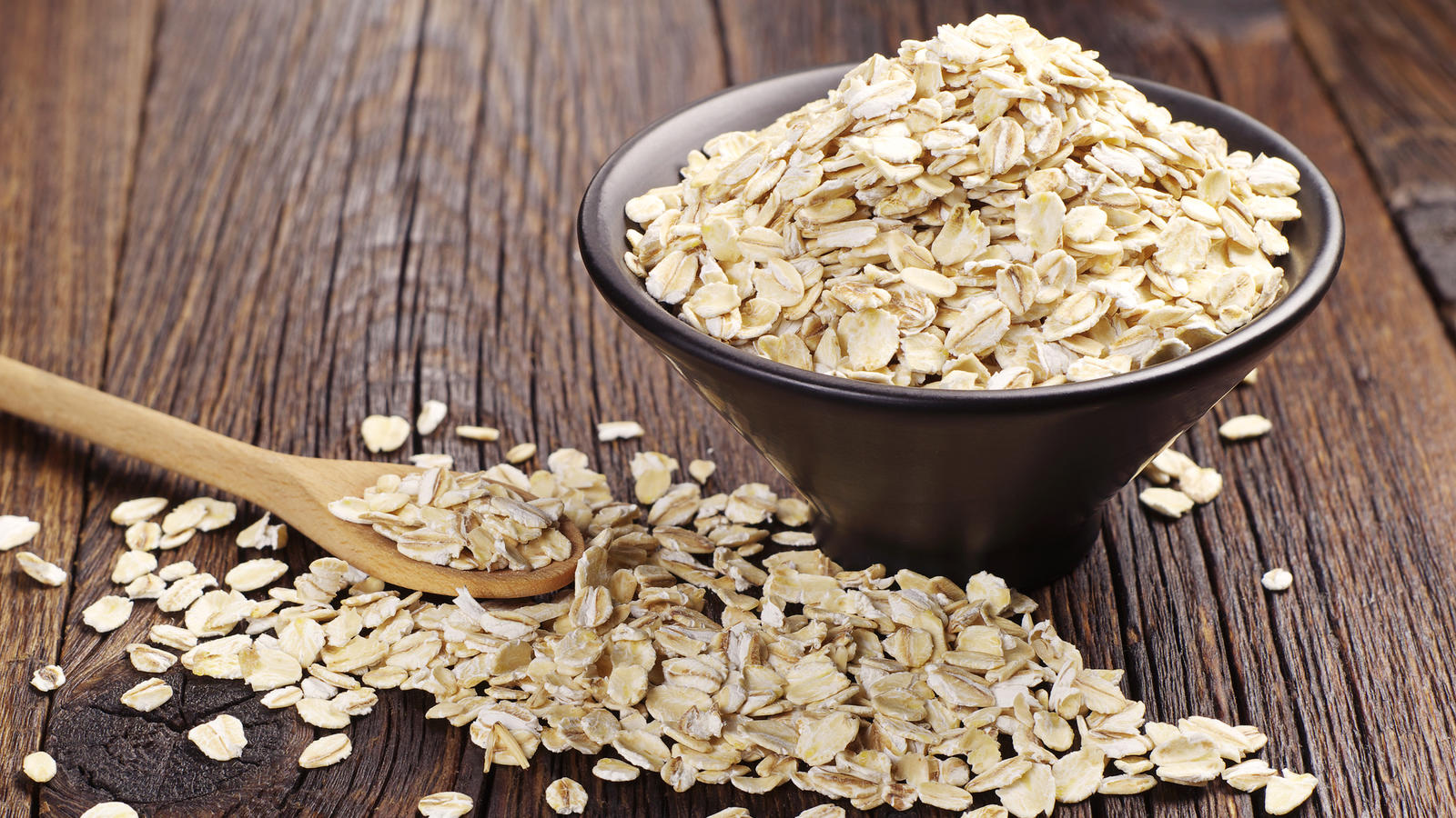 Oatmeal or oat flakes in black bowl and near on dark wooden table