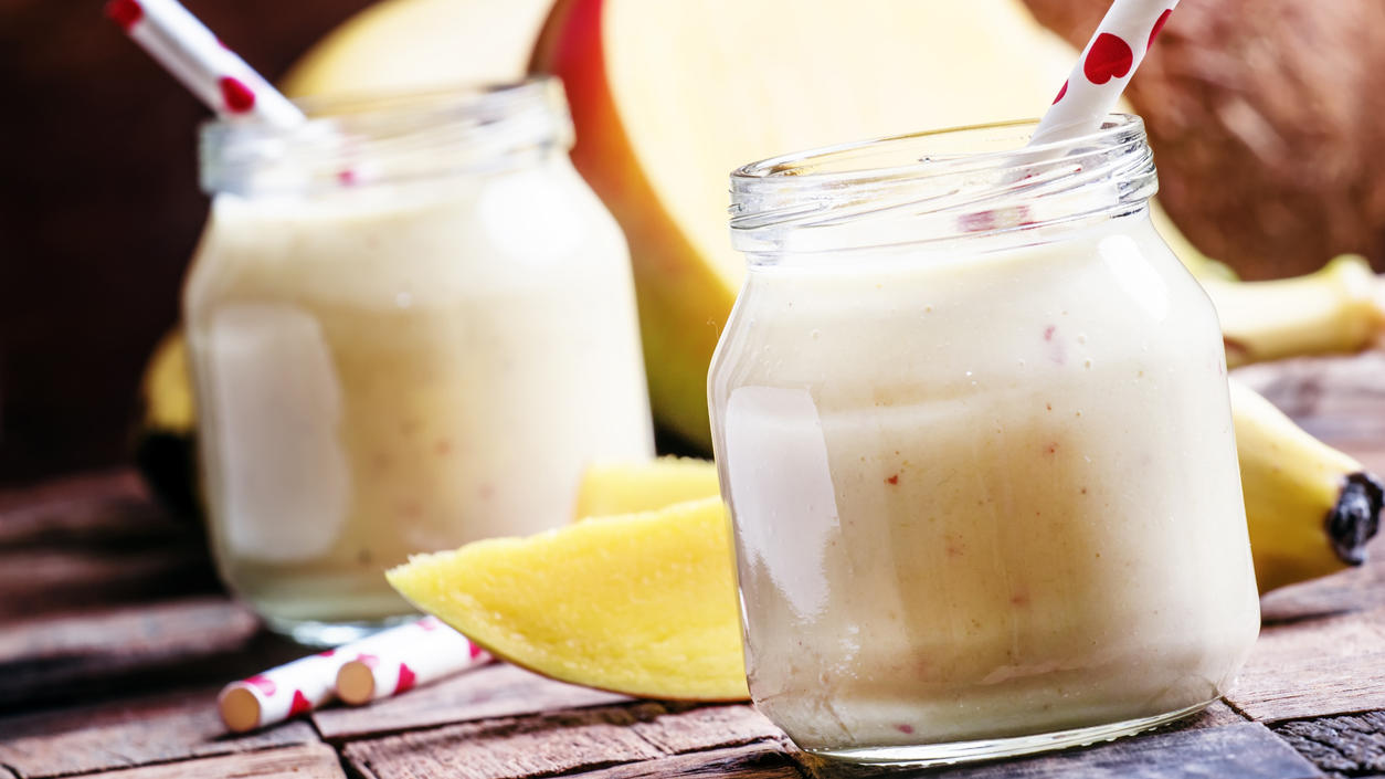 Banana mango smoothie with coconut in a glass jar, vintage wooden background, selective focus