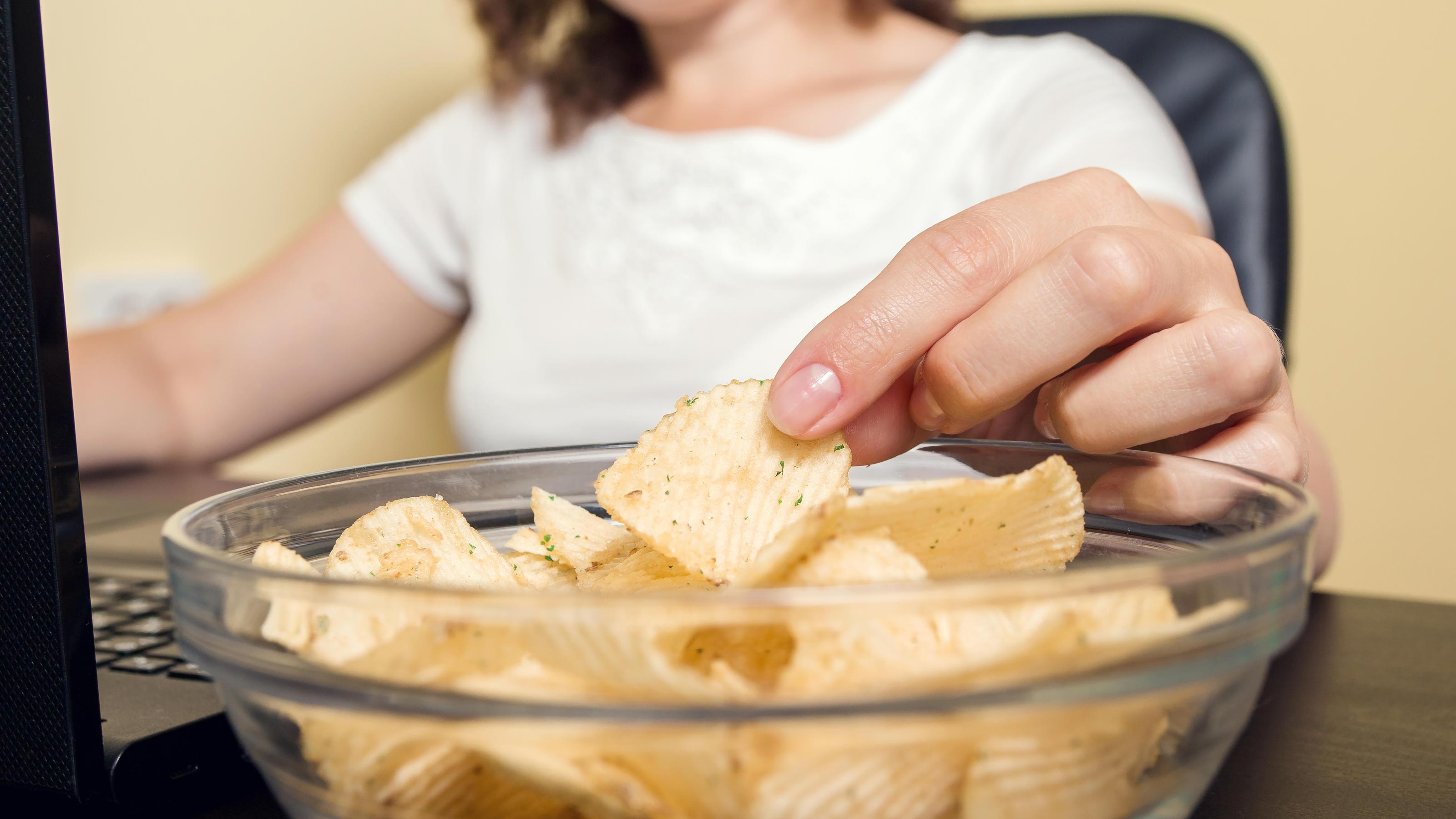 Junge Frau sitzt vor dem Laptop und greift nach Chips in einer Schüssel auf ihrem Schreibtisch